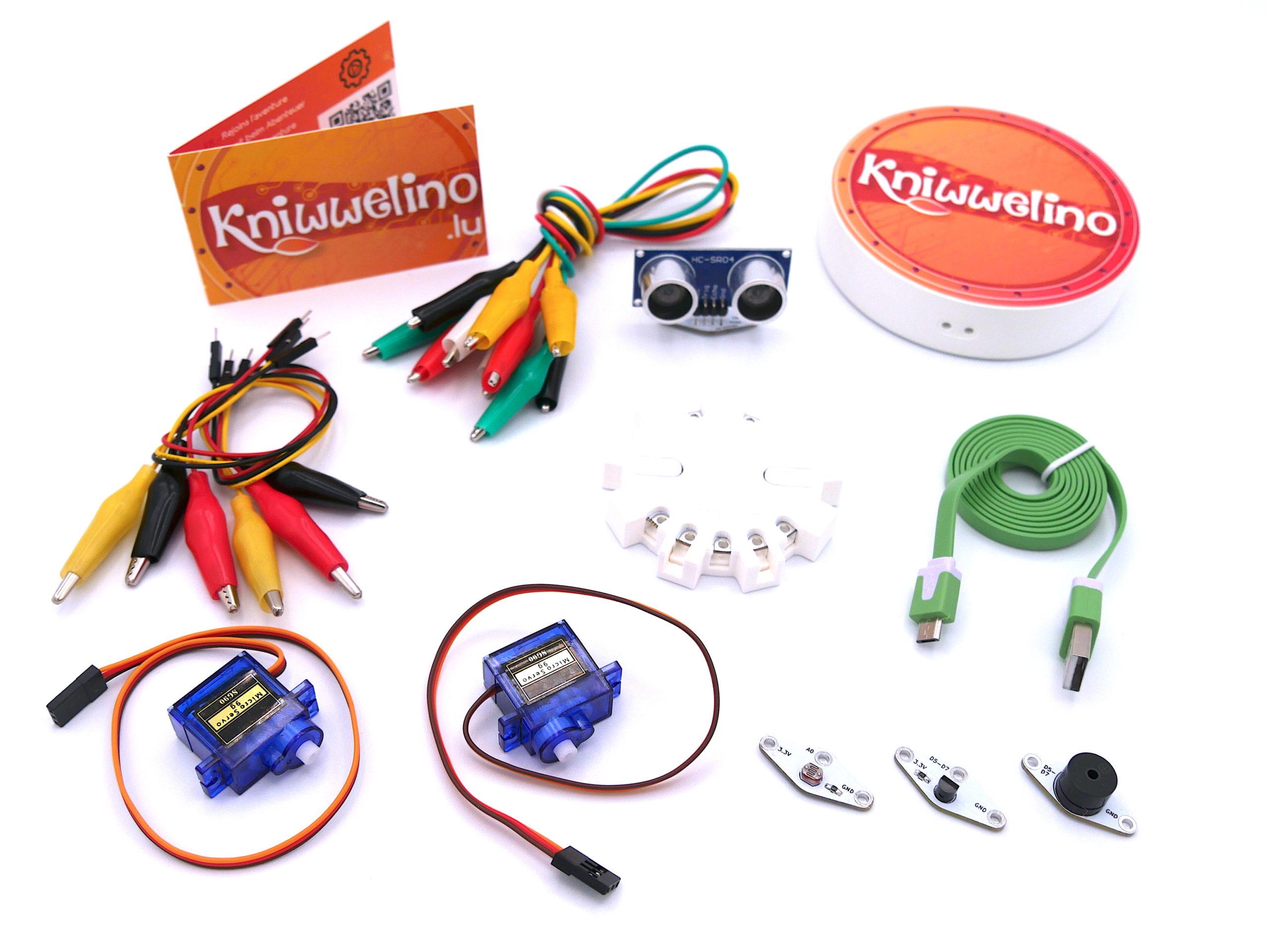 Contenu du My Explorer Kniwwelino Box avec une carte électronique/un kniwwelino, une batterie rechargeable, un câble USB, 5 pinces crocodiles simples, 6 pinces crocodiles spéciales, un capteur de distance, un capteur de température, un buzzer, 2 moteurs et leurs hélices.